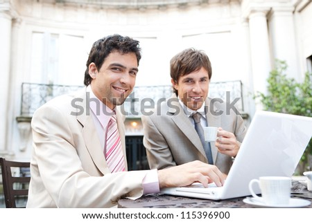 Two businessmen having a meeting while sitting in a classic coffee shop terrace, using a laptop computer and smiling at the camera. - stock photo