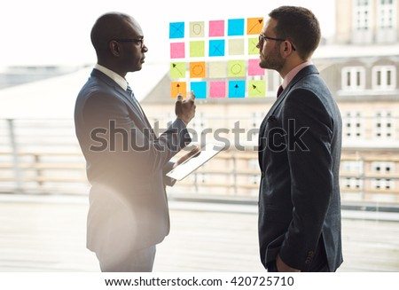 Two businessmen having a serious discussion as they stand in front of rows of colorful memos on a glass window brainstorming a new project - stock photo