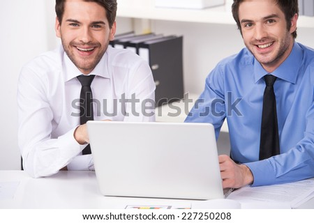 two businessmen having discussion in office. two smiling businessmen looking at camera with laptop - stock photo