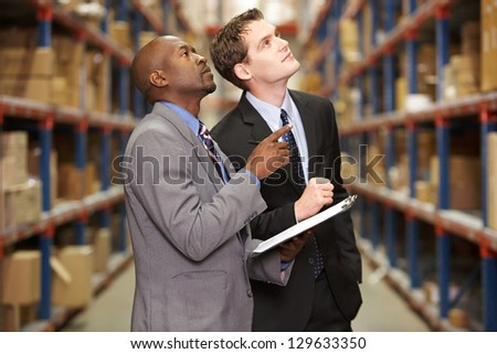 Two Businessmen Having Discussion In Warehouse
