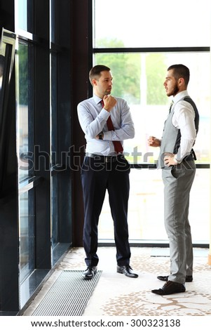 Two Businessmen Having Informal Meeting In Modern Office