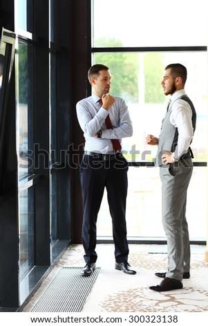 Two Businessmen Having Informal Meeting In Modern Office - stock photo