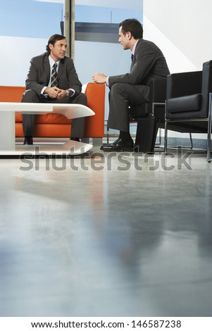 Two businessmen having meeting in office lobby - stock photo