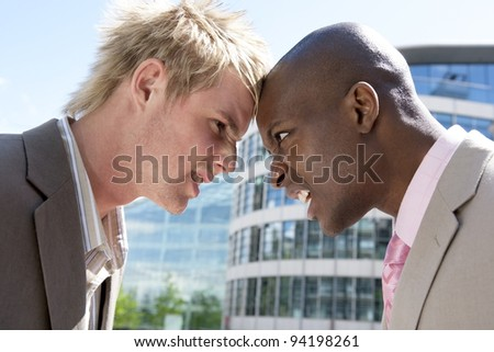 Two businessmen head to head in an argument in the city. - stock photo