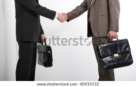 Two businessmen holding briefcases and shaking hands