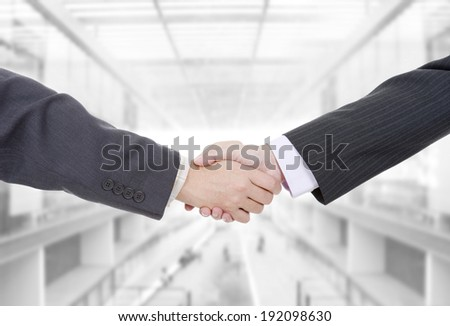 two businessmen in a handshake at the office - stock photo
