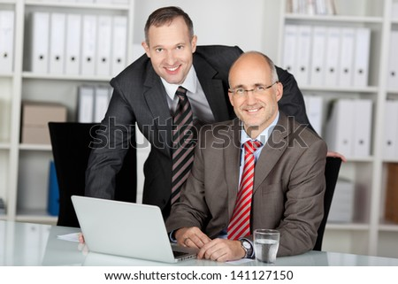 Two businessmen in an office smiling at the camera while working together behind a laptop computer - stock photo