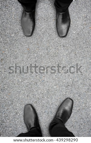 Two businessmen in black shoes standing on opposite sides. They are competitors, friends, rivals, enemies or partner. - stock photo