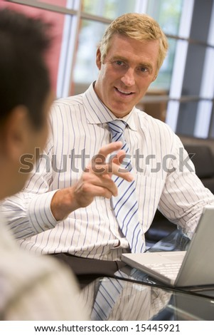Two businessmen in boardroom with laptop talking - stock photo