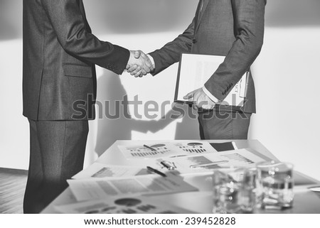 Two businessmen in formalwear handshaking after signing contract - stock photo