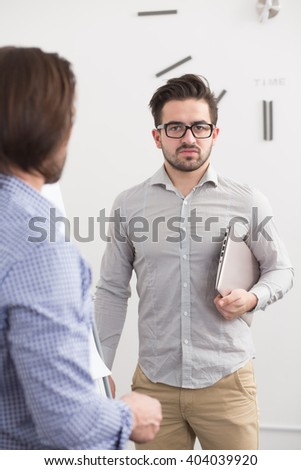 Two businessmen in office having discussion. Portrait of handsome man in glasses looking at camera and holding clipboard. - stock photo