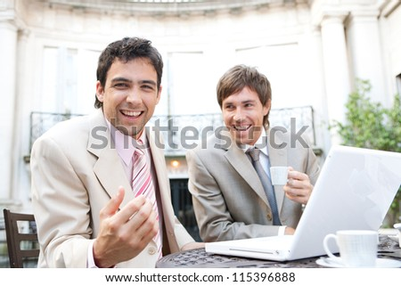 Two businessmen laughing while having a meeting in a classic coffee shop terrace, using a laptop computer. - stock photo