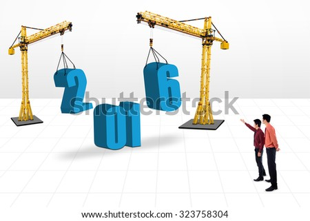 Two businessmen looking at the numbers 2016 under construction. Isolated on white background
