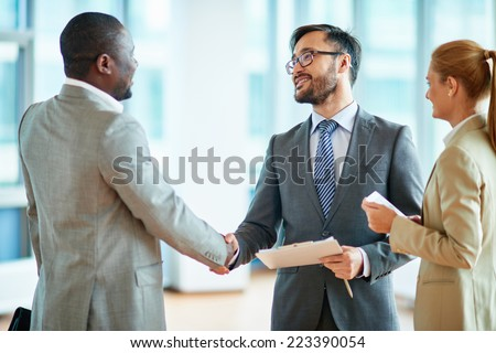 Two businessmen making agreement, their female colleague standing near by - stock photo