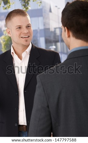 Two businessmen meeting outside of office building, smiling. - stock photo
