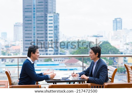 Two businessmen negotiating while sitting in the rooftop cafe - stock photo