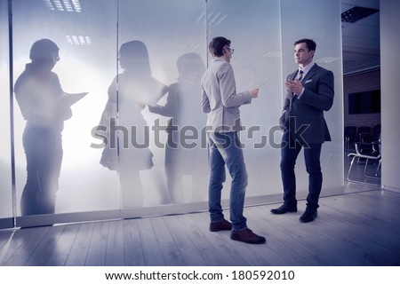 Two businessmen on the background of colleagues standing against window in office and speaking - stock photo