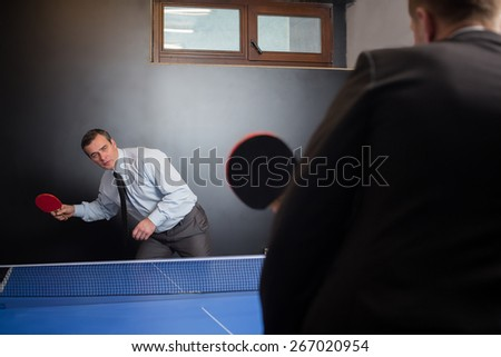 Two businessmen play tennis competition for relax in office - stock photo