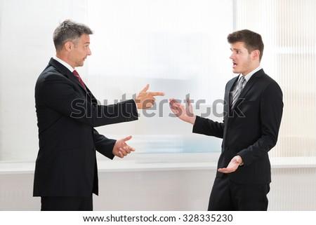 Two Businessmen Quarreling With Each Other In Office - stock photo