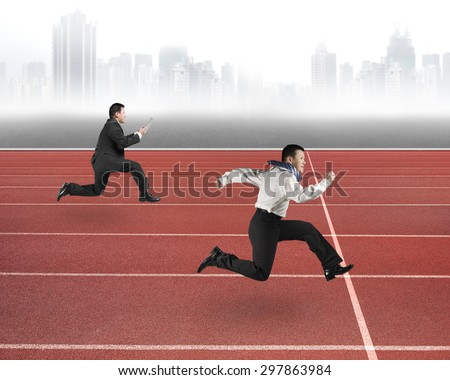 Two businessmen running on red track, with gray urban skyline background.