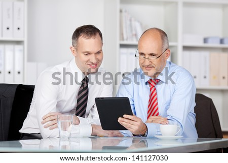 Two businessmen searching something using tablet computer - stock photo