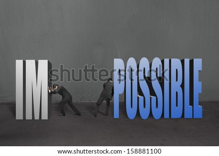 "Two businessmen separate word ""impossible"" to ""IM"" and ""POSSIBLE"" to make it possible in concrete wall background. - stock photo"