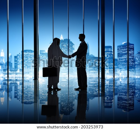Two businessmen shaking hand in the office building.