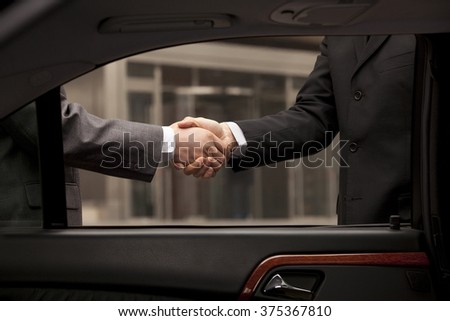 Two businessmen shaking hand through car window - stock photo