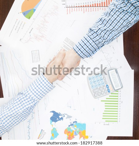 Two businessmen shaking hands above the desk - 1 to 1 ratio image - stock photo
