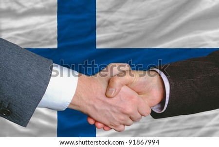 two businessmen shaking hands after good business investment  agreement in finland, in front of flag - stock photo