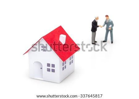 Two businessmen shaking hands and a little paper house.