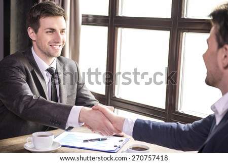 Two businessmen shaking hands during a business lunch. - stock photo