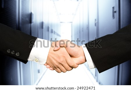 Two businessmen shaking hands in a technology data center - stock photo
