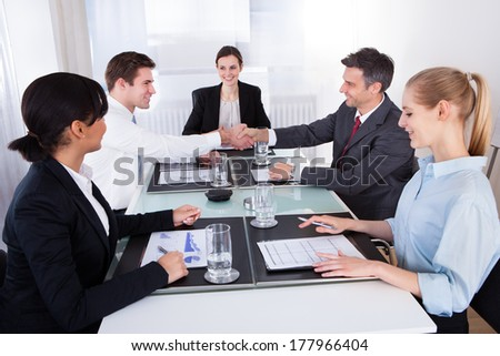Two Businessmen Shaking Hands In Front Of Colleagues At Conference - stock photo