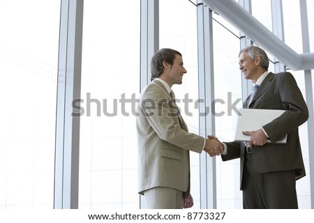 Two businessmen shaking hands in front of large glass windows, with one holding his laptop - stock photo