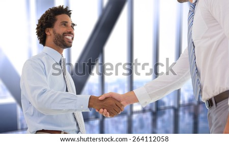 Two businessmen shaking hands in office against room with large window looking on city - stock photo