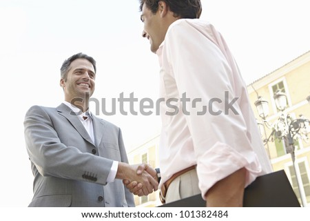 Two businessmen shaking hands in the city, smiling. - stock photo