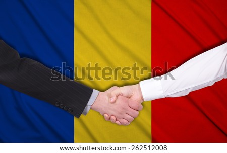 two businessmen shaking hands on Romania flag background - stock photo