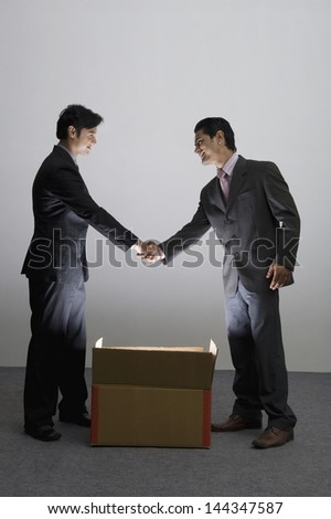 Two businessmen shaking hands over an illuminated cardboard box