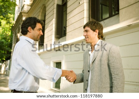 Two businessmen shaking hands while standing outdoors in a classic city financial district, looking happy. - stock photo