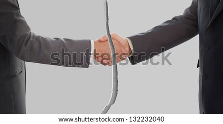 Two businessmen shaking hands with a tear down the middle - stock photo