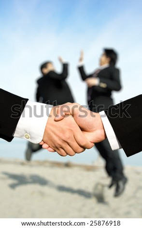 Two businessmen shaking hands with other two businessmen celebrating in the background, can be used for success concept