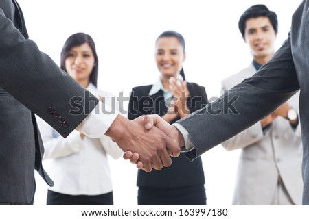Two businessmen shaking hands with their colleagues applauding - stock photo