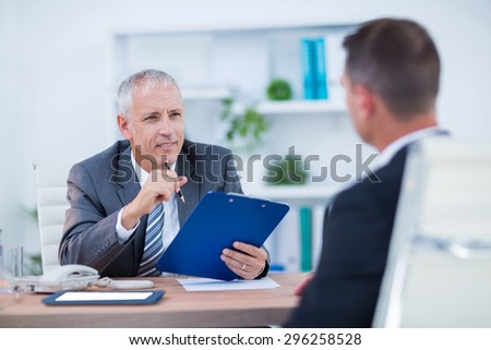 Two businessmen sitting and speaking and working at the office - stock photo