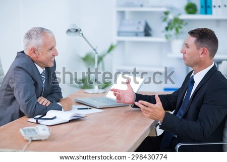 Two businessmen sitting and speaking in the office - stock photo