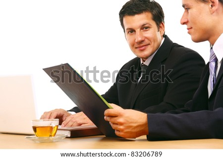 Two businessmen sitting at a table negotiating and signing a contract. - stock photo