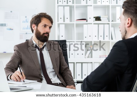 Two businessmen sitting at modern office desk with laptop and discussing future collaboration
