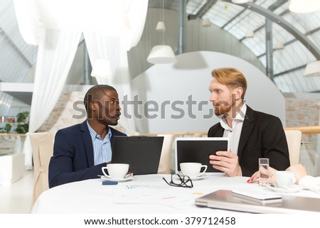 Two businessmen sitting at table in restaurant and speaking about business questions during business meeting. People using table PC. - stock photo