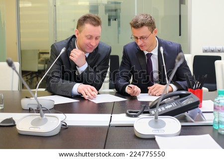 Two businessmen sitting at the table discussing documents - stock photo
