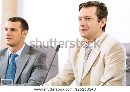 two businessmen sitting in a chair at the table, talk at the conference - stock photo
